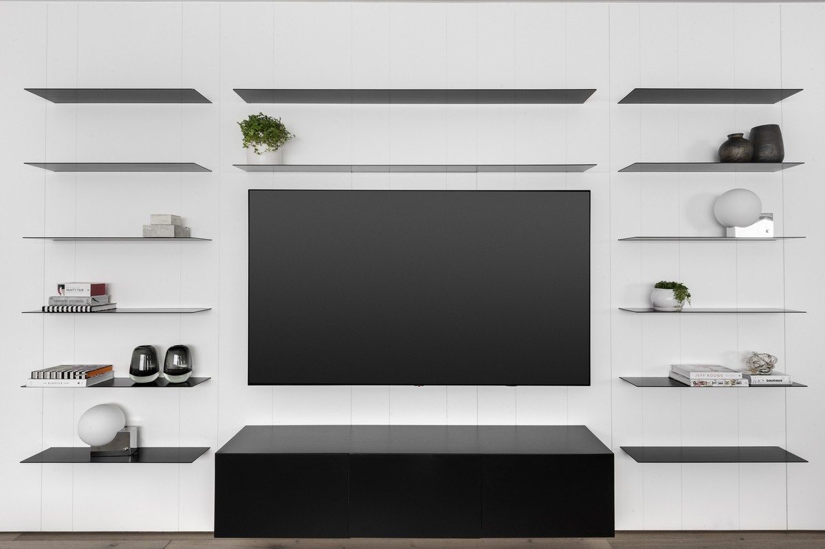 קיר טלוויזיה עם מדפי ברזל מעוצבים באזור ישיבה במשרד הביתי