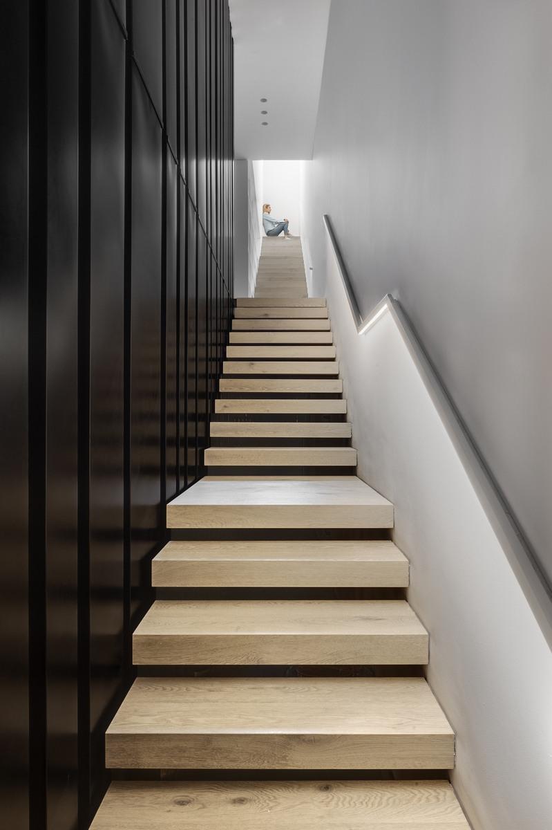 מדרגות עץ בשילוב מעקות ברזל ומחיצת ברזל